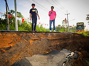 14 JULY 2015 - THAILAND: Motorists look at a collapsed roadbed in Ayutthaya province. The drought that has crippled agriculture in central Thailand is now impacting residential areas near Bangkok. The Thai government is reporting that more than 250,000 homes in the provinces surrounding Bangkok have had their domestic water cut because the canals that supply water to local treatment plants were too low to feed the plants. Local government agencies and the Thai army are trucking water to impacted communities and homes. Roads in the area have started collapsing because of subsidence caused by the retreating waters. Central Thailand is contending with drought. By one estimate, about 80 percent of Thailand's agricultural land is in drought like conditions and farmers have been told to stop planting new acreage of rice, the area's principal cash crop.       PHOTO BY JACK KURTZ