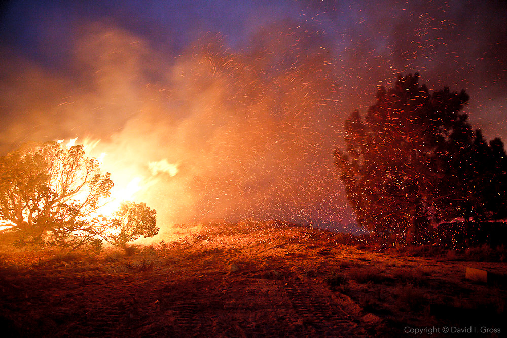 Embers from a backfire set by firefighters swarm across a fire break and threaten to spread the fire in the heavy winds during a night time controlled burn at the Station Fire, near Los Angeles. Weather is the least predictable of the factors that determine a wildfire, and a quick change in the wind can result in catastrophe.