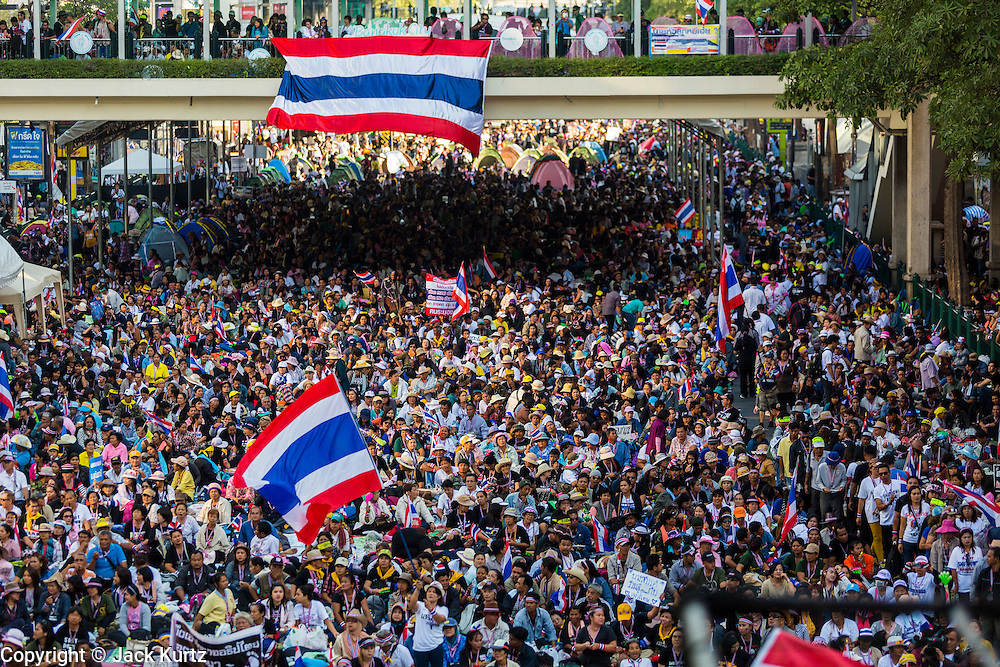 "13 JANUARY 2014 - BANGKOK, THAILAND: Anti-government protestors choke the Ratchaprasong Intersection, heart of Bangkok's high end retail shopping, during the first day of Shutdown Bangkok. Tens of thousands of Thai anti-government protestors took to the streets of Bangkok Monday to shut down the Thai capitol. The protest was called ""Shutdown Bangkok"" and is expected to last at least a week. The Shutdown Bangkok protest is a continuation of protests that started in early November. There have been shootings almost every night at different protests sites around Bangkok, including two Sunday night, but the protests Monday were peaceful. The malls in Bangkok stayed open Monday but many other businesses closed for the day and mass transit was swamped with both protestors and people who had to use mass transit because the roads were blocked.    PHOTO BY JACK KURTZ"