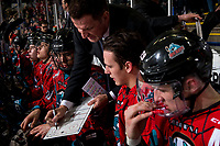 KELOWNA, CANADA - MARCH 16:  Kelowna Rockets' head coach Adam Foote goes over a play on the bench with Alex Swetlikoff #17 and Conner Bruggen-Cate #20 of the Kelowna Rockets against the Vancouver Giants on March 16, 2019 at Prospera Place in Kelowna, British Columbia, Canada.  (Photo by Marissa Baecker/Shoot the Breeze)