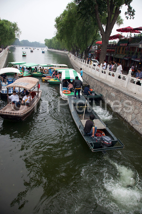 Boats causing a traffic jam at Yinding Bridge in the Shichahai area, near to Yandai Xiejie. Shichahai dates back to the Jin Dynasty. Around the lake there are ten famous Taoist and Buddhist temples and several formal royal mansions and gardens. The borders of the lakes are surrounded by large trees making Shichahai a famous scenic spot. In the summer tourists can rent boats to peddle on the lakes. In 1992 the municipal government of Beijing declared the district a Historical and Cultural Scenic District.