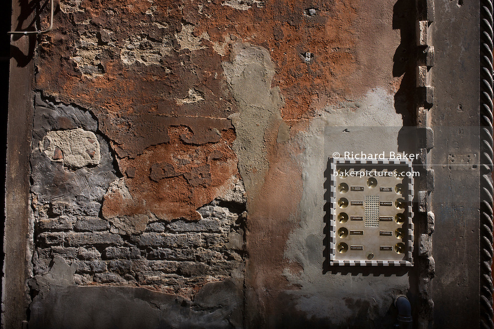 Peeling plaster and polished door bells in a narrow street in Castello, a district of Venice, Italy.