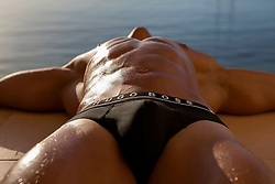 detail of a man's body ( crotch directly to camera) resting by the water