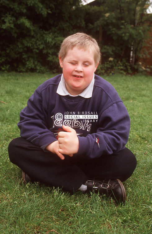 Portrait of young boy with Downs Syndrome sitting on grass in garden smiling,