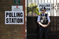 © Licensed to London News Pictures. 11/06/2015. London, UK. A police officer stands outside a polling station in Weavers near Brick Lane, Tower Hamlets, east London. Tower Hamlets residents go to the polls today to vote for a new Mayor of Tower Hamlets after Lutfur Rahman was removed from office for fraud and corrupt practices by an election court earlier this year. Photo credit : Vickie Flores/LNP