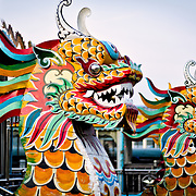 Brightly painted dragon heads that form the bowsprits of tourist boats moored on the banks of the Perfume River in Hue, Vietnam.