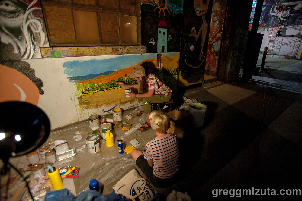 """Wyatt Wurtenberger works on his mural during Freak Alley Gallery's eight annual mural event in downtown Boise, Idaho on August 4, 2018. <br /> <br /> This was Wyatt's first year at Freak Alley. He was having a lot of fun and hopes to be back next year. His mural was based off one of his paintings but the sun was a new addition, it was originally going to be a hot air balloon. He likes to draw antennas and power poles since they show that people are present. This mural includes an antenna because he wanted something vertical to connect the two weird oblique areas of paint. He incorporates his signature """"WURT"""" into his works in a way that makes it hard to tell if it's part of the work of the painting or part of his name.<br /> <br /> Freak Alley Gallery's week long event provided an """"art-in-motion"""" experience as it welcomed the public to watch artists work on their murals."""