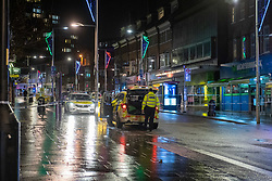 © Licensed to London News Pictures. 13/12/2020. London, UK. Police officers stand next to a vehicle inside the cordon on Station Road. Police were called at approximately 19:15GMT on Sunday, 13 December to reports of a stabbing in St Anns Road, Harrow. Officers and London Ambulance Service attended. <br /> A man – believed aged in his 20s – was found suffering stab injuries; despite the efforts of the emergency services he was pronounced dead at the scene. Two further males – both believed aged in their late teens – also suffered stab injuries. Photo credit: Peter Manning/LNP