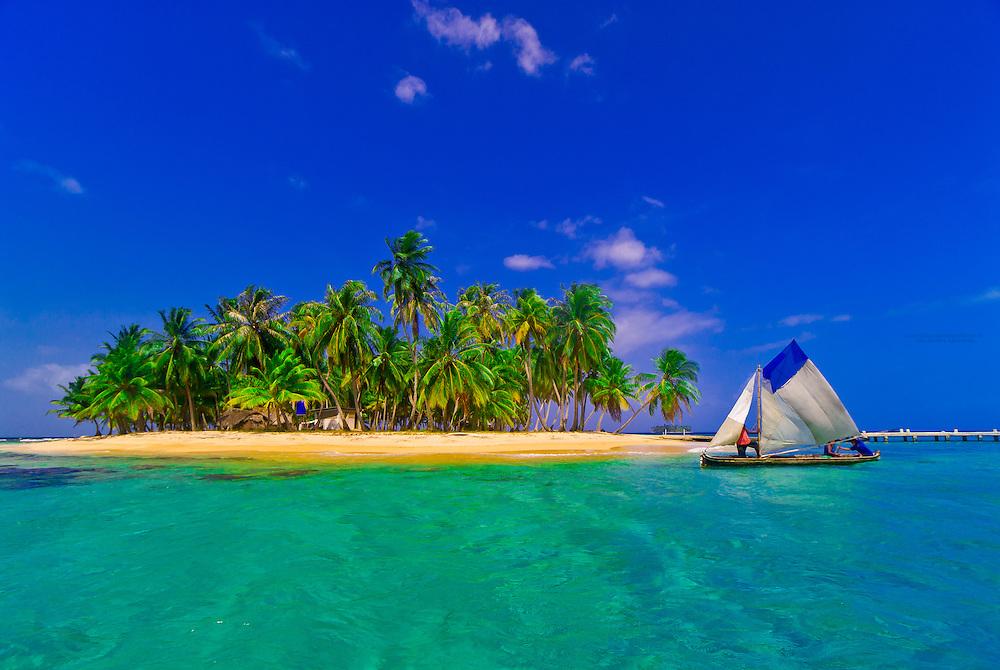 A Kuna Indian dugout canoe sailboat passes in front of the palm trees on Pelican Island (a.k.a. Icotupo Island), San Blas Islands (Kuna Yala), Caribbean Sea, Panama