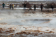 Tourists wait with cameras ready for the next eruption of the Strokkur geyser at Geysir in South-West Iceland