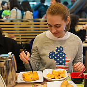 Girl eats dim sum and spring rolls in Michelin star fast food restaurant in Hong Kong