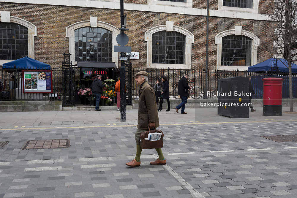 An elderly gentleman wearing Plus fours, a wax jacket, tweed flat cap and carrying a copy of the Times newspaper crosses Jermyn Street, SW1, on 5th March 2018, in London, England.