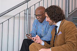 Two men talking steps cell phone meeting sitting