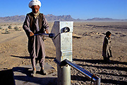 An elderly man, accompanied by a child, pumps water from a well in camp for Internally Displaced Persons called Zahri Dosht near Kandahar
