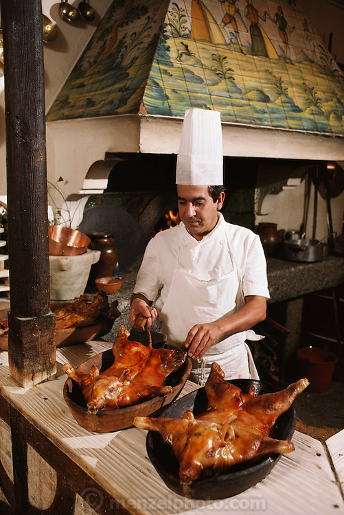 A chef preparing suckling pig in a traditional restaurant in Toledo, Spain.
