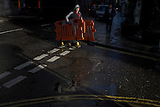 In strong sunlight, a workman delivers construction site fencing in the financial City of London's Threadneedle Street, crossing the road still wet after recent showers.