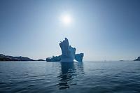 Sun shines in clear blue sky over iceberg, Sermilik Fjord, East Greenland