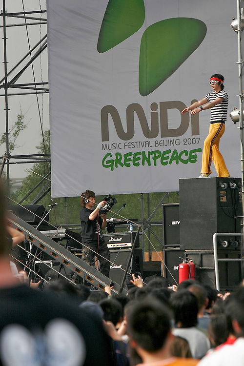 A performer jumps from stage and entertains the audience from the speakers during the Midi Festival in Beijing China 2007.  Midi is an  rock music festival held in northern Beijing catering to a small group of music listeners in China.  The festival lasts 4 days and gives performances from Chinese and international bands.