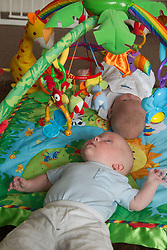 Twin babies on play mat baby gym.