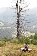 Isskogel mountain peak near Gerlos, Tyrol, Austria female hiker rests on a bench