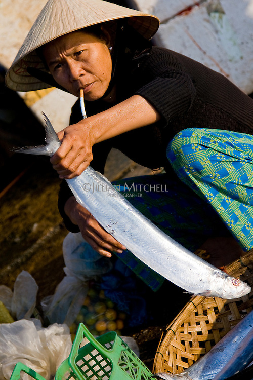 Woman displays one her fish for sale while smoking a cigarette.