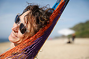 """SHOT 2/4/18 4:00:13 PM - Vesta Lingvyte of Denver, Co. relaxes on a hammock on Malpasos Beach in Sayulita, Mexico. Sayulita is a village about 40 km (25 miles) north of downtown Puerto Vallarta in the state of Nayarit, Mexico, with a population of approximately 5,000. Known for its consistent rivermouth surf break, Sayulita was """"discovered"""" by roving surfers in the late 1960s with the construction of Mexican Highway 200. Still a mecca for beginning surfers of all ages, Sayulita also attracts tourists to its numerous art galleries and casual and hipsters cafes and restaurants. (Photo by Marc Piscotty / © 2018)"""
