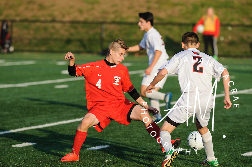 Belmont's Colby Brown kicks the ball past Steven's Connor Whipple in the NHIAA Division III semi-final game at Laconia High School on Wednesday, November 2, 2016.  (Alan MacRae/for the Laconia Daily Sun)