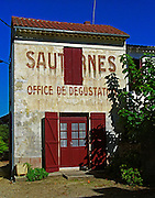 A building in the village of Sauternes, Sauternes Office de Degustation (Wine Tasting Office) written on the wall. The building looks rather dilapidated and a window has been cut through the text Sauternes. Bordeaux Gironde Aquitaine France Europe