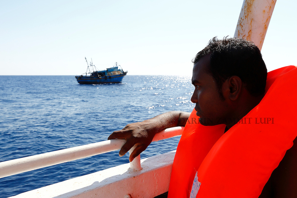A migrant on the Migrant Offshore Aid Station (MOAS) ship MV Phoenix looks at the wooden boat from which he was rescued 10.5 miles (16 kilometres) off the coast of Libya August 6, 2015.  An estimated 600 migrants on the boat were rescued by the international non-governmental organisations Medecins san Frontiere (MSF) and MOAS without loss of life on Thursday afternoon, according to MSF and MOAS, a day after more than 200 migrants are feared to have drowned in the latest Mediterranean boat tragedy after rescuers saved over 370 people from a capsized boat thought to be carrying 600.<br /> REUTERS/Darrin Zammit Lupi <br /> MALTA OUT. NO COMMERCIAL OR EDITORIAL SALES IN MALTA