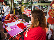 "18 JANUARY 2017 - BANGKOK, THAILAND: A traditional Chinese calligrapher draws New Years greetings that she sells in Bangkok's Chinatown district, before the celebration of the Lunar New Year. Chinese New Year, also called Lunar New Year or Tet (in Vietnamese communities) starts Saturday, 28 January. The coming year will be the ""Year of the Rooster."" Thailand has the largest overseas Chinese population in the world; about 14 percent of Thais are of Chinese ancestry and some Chinese holidays, especially Chinese New Year, are widely celebrated in Thailand.<br />       PHOTO BY JACK KURTZ"
