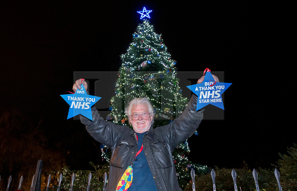 """© Licensed to London News Pictures; 17/11/2020; Bristol, UK. TONY MILES (a.k.a. Smiley Miley of Radio 1 Roadshow) holds stars to be placed on a giant Christmas tree for the """"Florence NHS Christmas Tree"""" Thank You NHS Stars Fundraiser, with blue stars signed by among others the UK Prime Minister Boris Johnson, Health Secretary Matt Hancock and Deputy Chief Medical Officer Jonathan Van-Tam. For the 10th year Clifton Village in Bristol has a 50ft illuminated Christmas tree, the tallest in any UK village. Photo credit: Simon Chapman/LNP."""