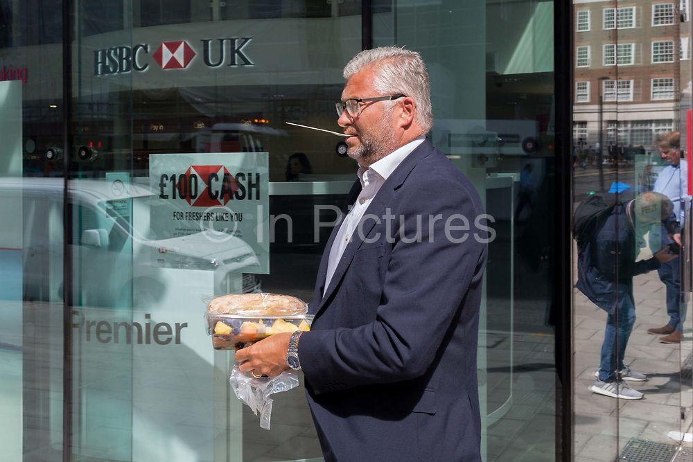 Passing a branch of a HSBC bank, businessman on his lunch-break carries his takeaway back to his office with a wooden spoon in his mouth on Moorgate in the City of London, the capitals financial district - aka the Square Mile, on 8th August, in London, England.