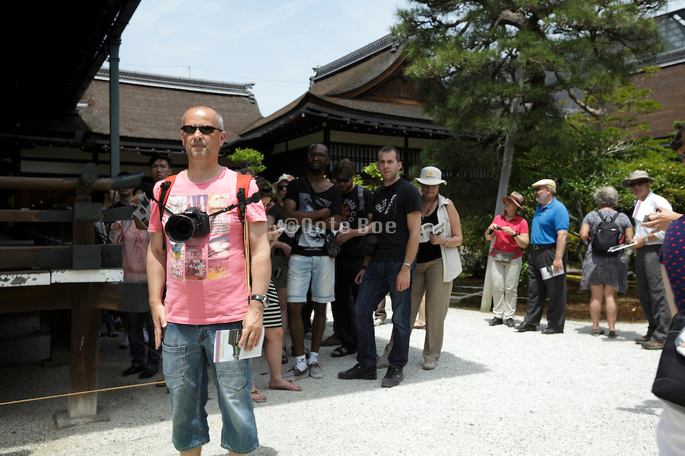 Western tourists at the Kyoto Imperial Palace grounds on a hot and sunny day Japan