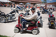 Santa Rosa resident Bill Bates eyes the motorcycles as he rides his rascal scooter along Parker Ave during the Smoke Out motorcycle rally on Saturday, June 19, 2010.