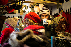 © Licensed to London News Pictures . Manchester , UK . A woolly hat stall holder sips on a hot drink from a mug . FILE PHOTO DATED 20/11/2013 of Christmas Markets in Manchester as temperatures drop and 2014 seasonal markets start up across the country , selling mulled wine , german hot dogs , dutch pancakes , wooly hats and many other festive frivolities . Christmas markets provide an economic boost to many city centres and create a festive atmosphere on otherwise cold and dark nights . . Photo credit : Joel Goodman/LNP