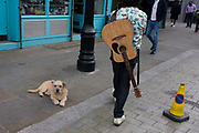 A guitar man walks through a Waterloo street with a dog sitting on the pavement. Carrying his musical instrument on his back, the man continues his way through this district of south London where buskers are common. The dog seems relaxed and comfortable to be stretched out on the pavement.