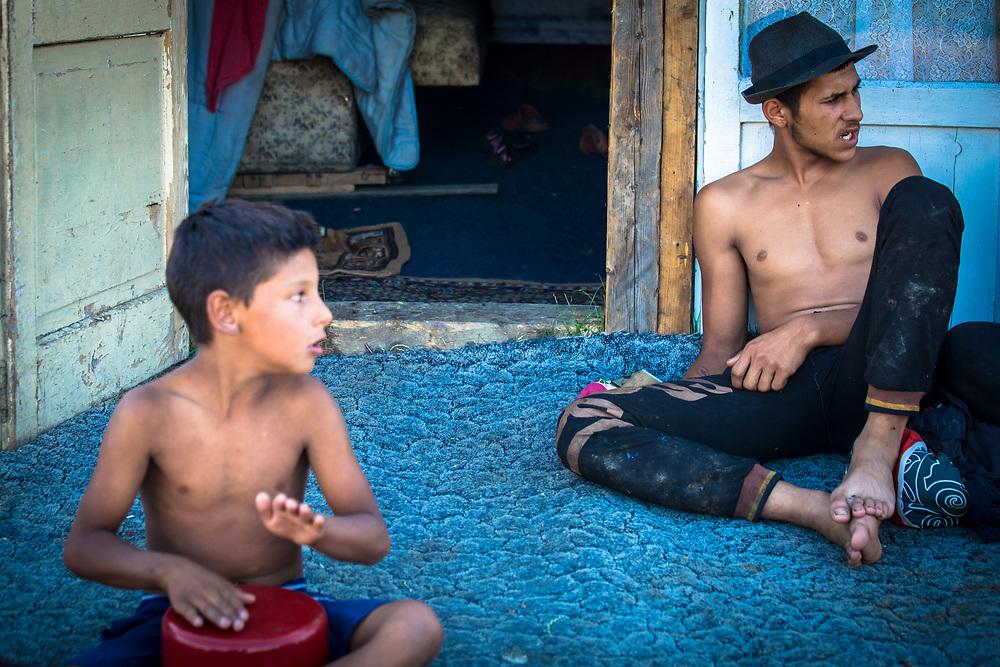 Sergio (19) and his son Emmanuel (7) rest outside their makeshift home in a slum built next to the Pata Rat garbage dump.                                                                       © Daniel Barreto Mezzano
