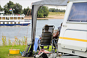 Nederland, Gendt, 1-8-2015 Kamperen bij de rivier,water. Op vakantie in eigen land. Een rondvaartboot voor de rivier, de Prinses Juliana, vaart juist voorbij met dagjesmensen. Foto: Flip Franssen/HH