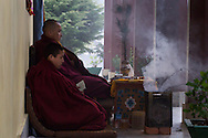 Monks sit outside a monastery entry where the grandmaster is having a 24 hour prayer session before he goes into isolation for three years, three months, three days and three minutes. Kurje Lhakhang, Bhutan 2014