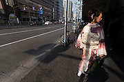 A woman wearing a kimono walks in the street near Tsukiji, Tokyo, Japan. Sunday March 22nd 2015