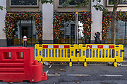In an otherwise empty City of London financial district, whose workforce are largely still working from home during the second (Autumn) spike Coronavirus pandemic, a single person walks past social distance pavement-widening bariers outside a closed City bar at lunchtime on Gresham Street, on 5th October 2020, in London, England.