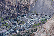 See the Gunnison River far below Dragon Point, in Black Canyon of the Gunnison National Park, near Montrose, Colorado, USA. The canyon exposes you to some of the steepest cliffs, oldest rock, and craggiest spires in North America. With two million years to work, the Gunnison River, along with the forces of weathering, has sculpted this vertical wilderness of rock, water, and sky.