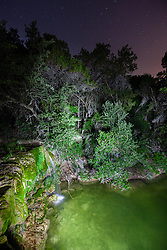 Light painted night waterfall on Little Bee Creek, Los Madrones Ranch in the Hill Country, Texas, USA.