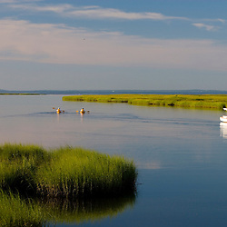 Kayakers paddle past a sailboat at anchor between Great Island and the shoreline in Old Lyme in the Connecticut River.  Near mouth of the river in Old Lyme, Connecticut.  Salt Marsh.