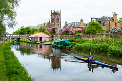 View of the Union Canal with woman in canoe at Polwarth in Edinburgh, Scotland, United Kingdom