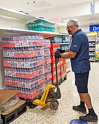 © Licensed to London News Pictures 23/07/2021. Sidcup, UK. A member of staff working hard to restock bottled water. Empty shelves in the water aisle at Sidcup Tesco in South East London. Shoppers continue to seeing a shortage of bottled water in supermarkets today as supplies have been hit by staff being forced to self-isolate. Photo credit:LNP
