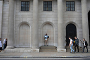 Man standing on a wall outside the Bank of England vaping as people pass by, in the City of London, United Kingdom.