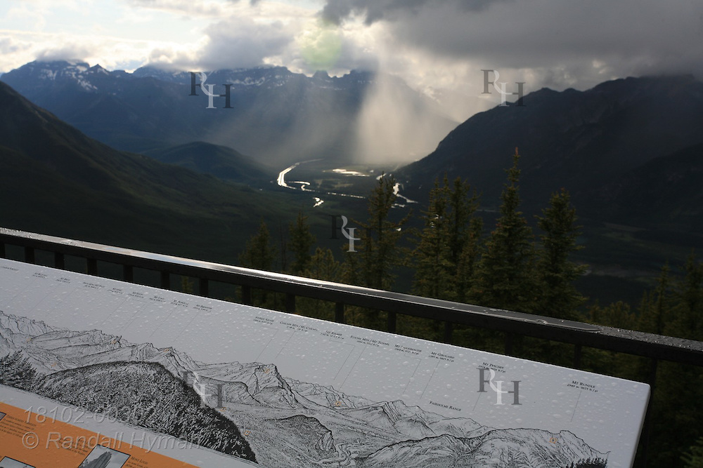 Panoramic locator signage boardwalk atop Sulphur Mountain frames view of summer thunderstorm over the Bow River Valley; Banff, Alberta, Canada.