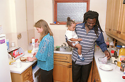 Father and mother preparing food in kitchen with young daughter,