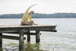 Woman doing yoga on boardwalk at the lake, Ammersee, Upper Bavaria, Germany